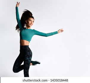 Young athletic woman brunette girl in a good shape with hair in a ponytail in trendy camo sportswear gym uniform jumps dances does exercises workout isolated on gray background
