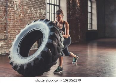 Junge Sportlerin mit einem Cross-Ffit-Rad in Innenräumen