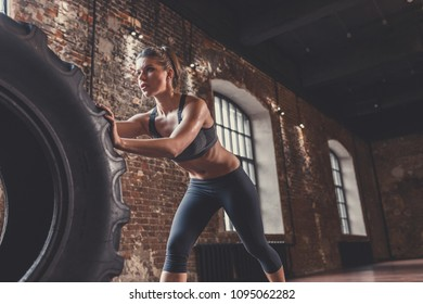Young athletic woman with a crossfit wheel indoors