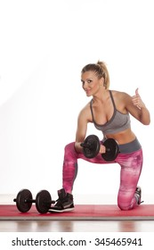 young athletic woman doing exercises with weights and showing thumbs up
