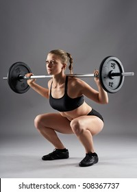 Young athletic woman doing squats with the barbell on gray background