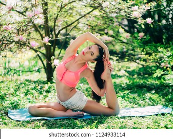 Young athletic woman doing stretching exercises in the park