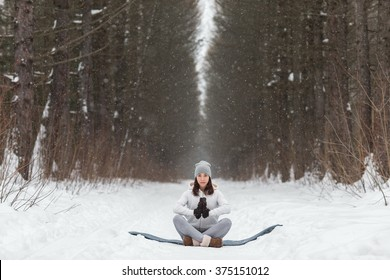 Young athletic woman doing yoga in the woods in winter. Beautiful girl engaged in fitness in winter park.