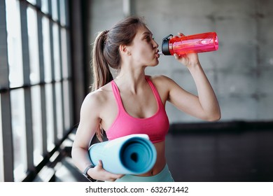 Young athletic woman drinking water in gym.
