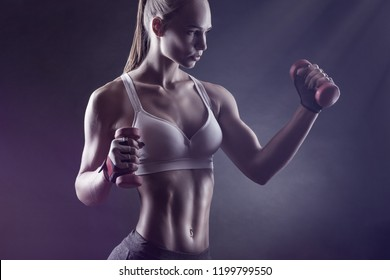 Young athletic woman with dumbbells against a dark background