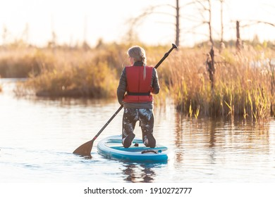 Young athletic woman enjoy doing SUP stand up paddle boarding at sunset in lake. Summer evening activity