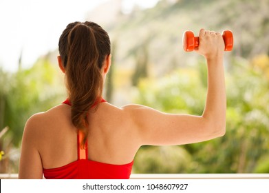 Young athletic woman exercising on verandah: overhead press for upper body strength