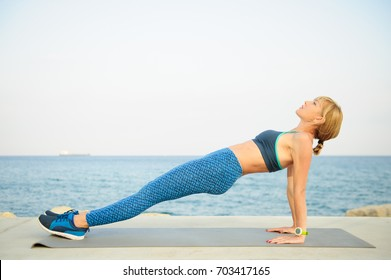 Young athletic woman exercising outdoors: reversed plank for total body strength