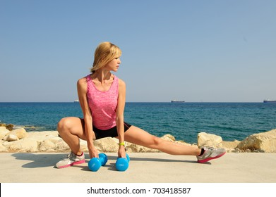 Young athletic woman exercising outdoors: side lunge with weight for flexibility and strength