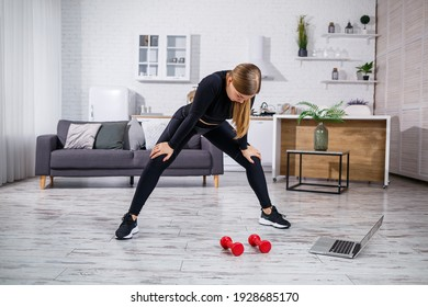 Young athletic woman in fitness clothes black top and leggings in an apartment using online workout from a fitness site on a laptop and doing sports at home. Fitness at home during quarantine