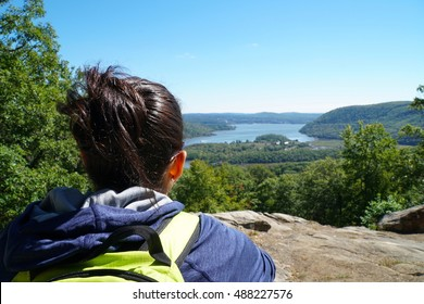 A young athletic woman hiking up a mountain sits to rest on a large rock overlooking the beautiful view of the Hudson River