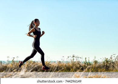 Young athletic woman jogging on rural road in early morning. Sporty girl in black training clothes running toward the sun. Photo with copy space on blue sky background. Full-length portrait