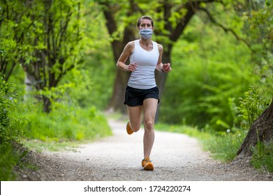 Young and athletic woman jogging outdoor in the nature, she have pois protective mask on face, shorts and short shirt. Running alone on a tree-lined road in the days of the Corona Virus or Covid-19.