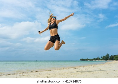 Young athletic woman jumping up on a tropical beach