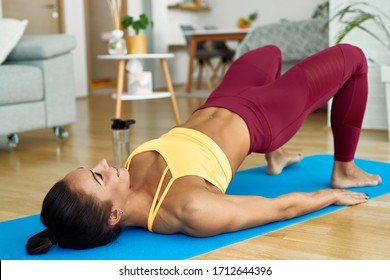 Young athletic woman lifting her hips while doing glute bridge exercise on the floor at home.
