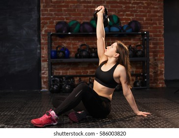 Young athletic woman performing Turkish Get Up exercise with a kettlebell at the gym