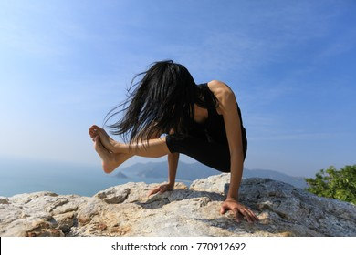 Young athletic woman practicing outdoor yoga arm-balance handstand crane crow pose