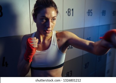 Young athletic woman preparing for kickboxing training and warming up in locker room.