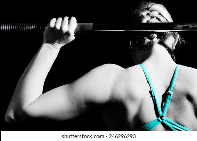 Young athletic woman pumping up muscles with barbell. black and white