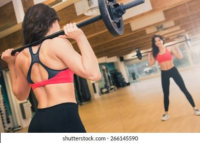 Young athletic woman pumping up muscles with barbell in the gym. Weight training.