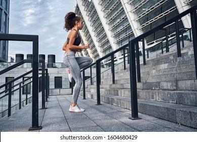 Young athletic woman running upstairs, jumping training at urban city stadium