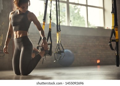 Young athletic woman in sports clothing adjusting trx fitness straps while training in the gym.