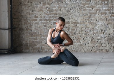 young athletic woman in sportswear doing yoga exercise - Bharadvaja's Twist in yoga class