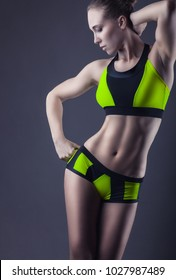 Young athletic woman in sportswear poses for the camera against a black background