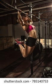 Young athletic woman with strong fit and toned body wearing sports top and shorts doing butterfly pull-ups at crossfit functional training gym bar fitness toning power strengthening agility effort