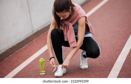 A young athletic woman in a tracksuit bent over tying sneakers on a treadmill, getting ready for a run. Next to the foot is a green sports bottle. Copyspace.