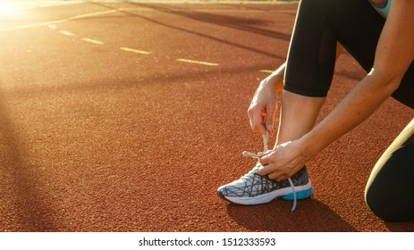 young athletic woman tying her shoe before she starts running on the hard court