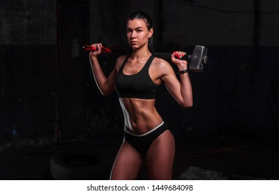 Young athletic woman workout tire wheel indoors with hammer on her shoulders on dark background. Concept cardio Fitness.