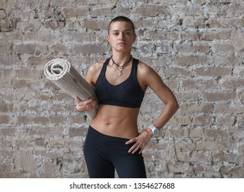 young athletic woman with yoga exercise mat standing near brick wall, looking at camera