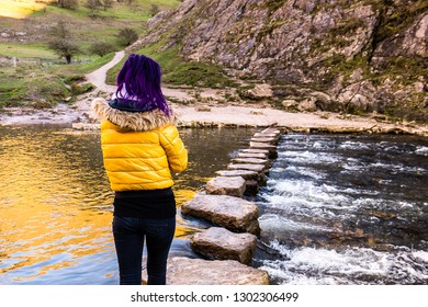 A young athletic women crosses over a fast flowing river using some stepping stones in the icy cold day in January, keeping her balance on the icy rocks