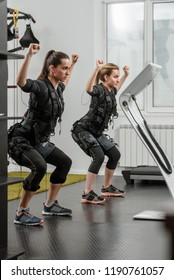 Young athletic women in EMS suits exercising in modern gym