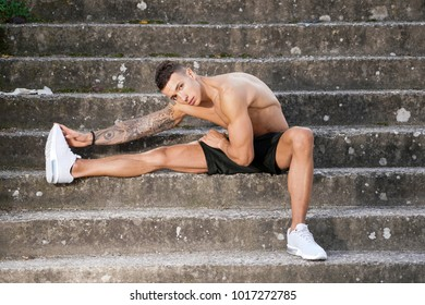 Young and athletics man shirtless after workout stretching his right leg on the outdoor stairs in white sneakers and black shorts shirtless after workout  showing his muscles and tattoos.