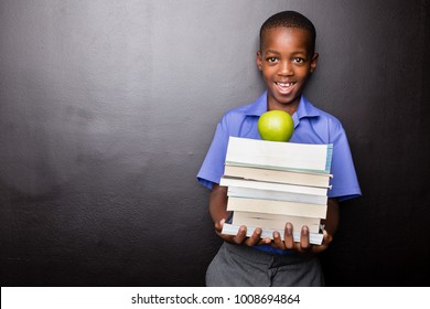 Young atractive black boy wearing school unifor while holding his school books and a green apple, looking excited about going back to school.