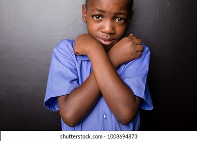 Young atractive black boy wearing school unifor looking sad while hugging himselfin a  worried manner, going back to school.