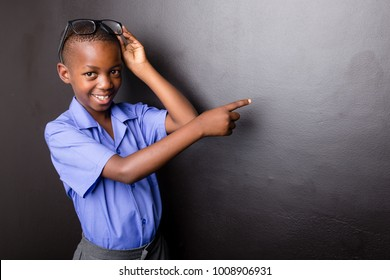 Young atractive black boy wearing school unifor and glasses looking excited about going back to school pointing with his finger in a direction.