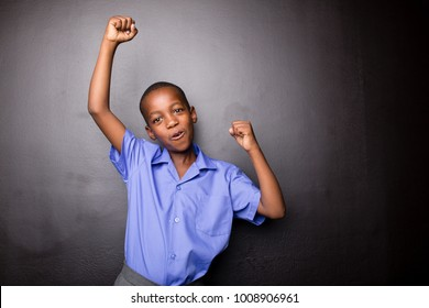 Young atractive black boy wearing school unifor looing strong and configent going to school for the first time with his arms in a air fist pump motion.