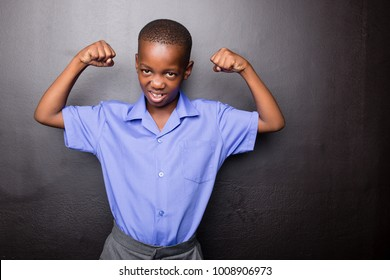 Young atractive black boy wearing school unifor looing strong and configent going to school for the first time with his arms in a muscle flexing gesture..