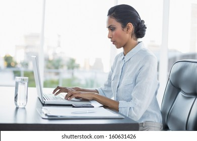 Young attentively working businesswoman sitting at her desk in the office
