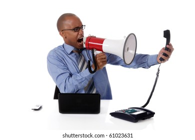 Young attractive African American businessman in office at his desk, yelling angry into megaphone at a telephone receiver . Studio shot. White background.