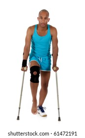 Young attractive African American man athlete on crutches, wearing a wrist brace and knee support,  bandaged. White background. Studio shot.