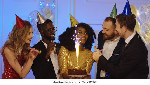 Young attractive african american woman with a birthday cake among her mixed races friends with party equipment. Portrait of celebrating people. Indoor
