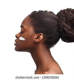 Young attractive African girl with a smear of cream on her face. Skin care concept.