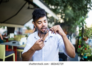 Young attractive afro American businessman  sitting in cafe bar and cleaning glasses.