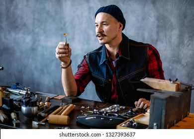 young attractive artisan checking the quality of amber in the jewellery shop, close up photo, working time