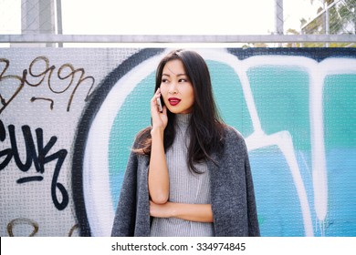 young attractive Asian business woman talking on the phone on the background wall with graffiti