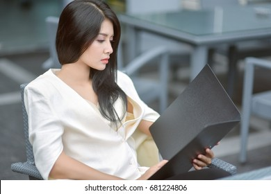 Young attractive Asian business woman sleeping, drowsing or taking a nap at her desk, Tired business woman accountant with bills and paper folders in office, tired young business woman with laptop.